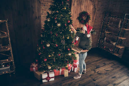 Top above high angle photo of positive brunette hair girl hand bauble on evergreen fir tree prepare for christmas celebration party wear santa claus hat in house with newyear decoration lights indoors Stock fotó