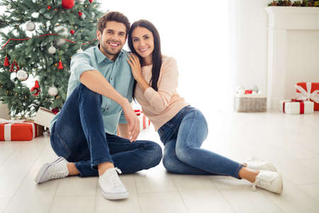 Portrait of two people charming couple sitting on floor enjoy christmas time x-mas holidays wearing blue denim jeans shirt pastel jumper in house indoors
