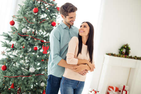 Turned photo of two people charming spouses with brunet hair hug enjoy christmas time x-mas holidays wearing blue denim jeans pink pullover in house with newyear decoration wreath indoors Stock Photo