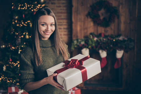 Close up photo of positive cheerful girl hold gift box from christmas father fairy north pole creature enjoy newyear time celebration in house full of x-mas lights illuminations garlands indoors