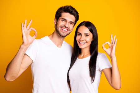 Photo of amazing marriage pair showing okey symbols agree with good quality product wear casual outfit isolated yellow color background