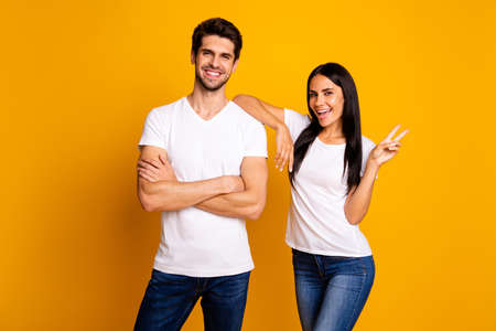 Photo of amazing couple working together best team showing v-sign symbol wear casual t-shirts and jeans isolated yellow color background