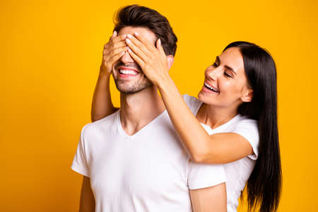 Guess who. Photo of amazing lady hiding eyes macho guy making unexpected surprise wear casual white t-shirts isolated yellow color background