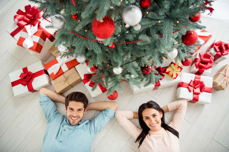 Top above high angle photo of two charming romantic people with brunette hair lying on floor enjoying christmas time x-mas holidays in house with giftboxes indoors