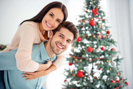 Close up photo of two people cheerful romantic man carry his sweetheart piggyback enjoy christmas time x-mas holidays in house indoors