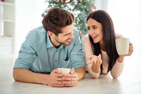 Close up photo of two people charming lady and guy hold mug hot beverage lying on floor in house indoors enjoy christmas time x-mas holidays