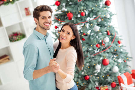 Portrait of two people cheerful man and woman dance enjoy christmas vacation x-mas holidays in house with newyear decoration indoors