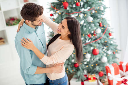 Top high angle photo of two charming romantic people dance enjoy christmas time x-mas vacation in house with evergreen fir tree and giftboxes indoors