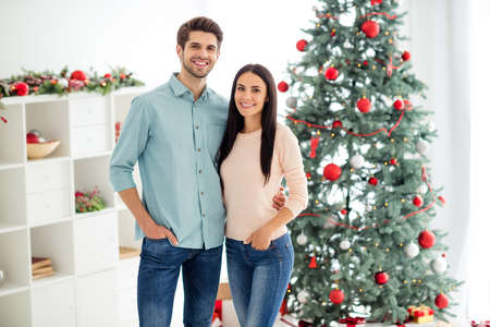 Portrait of two charming romantic people hug enjoy christmas time x-mas holidays wearing pink blue pullover denim jeans in house with noel decoration indoors