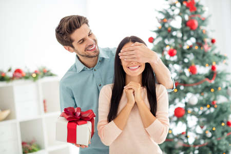 Portrait of two people romantic woman wait for christmas package giving by her husband enjoy noel x-mas tradition in house indoors
