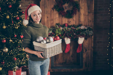 Portrait of positive cheerful dreamy girl in santa claus hat knitted jumper hold box with many christmas toys want decorate evergreen fire tree to prepare newyear time celebration in house indoors