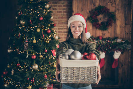 Here want me help. Portrait of positive brown hair cheerful girl hold box with many baubles to prepare for christmas time celebration in house full of newyear garlands ornaments indoors