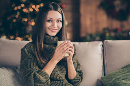 Close up photo of dreamy peaceful calm girl in warm soft sweater hold mug cup with cacao eggnog enjoy christmas vacation celebration sit divan in house full of christmastime decoration indoors