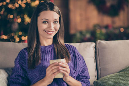 Close up photo of positive girl wear knitted sweater hold mug cup with hot beverage enjoy her christmas pause vacation in house full of newyear lights decoration sit on divan with cushions Stok Fotoğraf