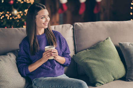 Portrait of peaceful calm girl sit on divan look enjoy christmas celebration hold cup mug with eggnog in house full of newyear decoration