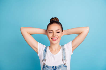 Top high angle photo of lovely youth with her eyes closed wearing white t-shirt denim jeans overalls isolated over blue background