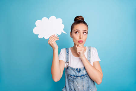 Portrait of concentrated person holding papercard bubble touching her chin wearing white t-shirt denim jeans overalls isolated over blue background Banco de Imagens