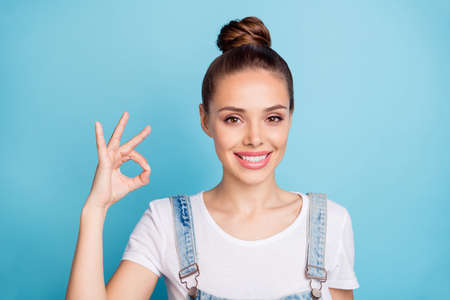 Close up photo of confident lady showing ok sign smiling wearing white t-shirt denim jeans overall isolated over blue background