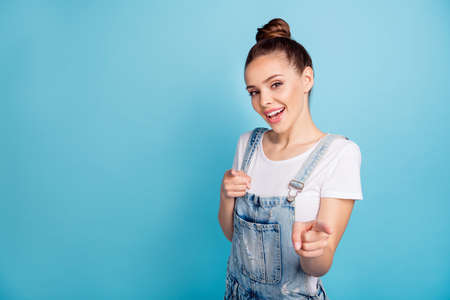 Portrait of funky lady pointing at yourself wearing white t-shirt denim jeans isolated over blue background Banco de Imagens