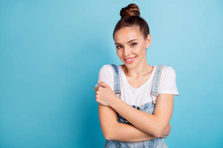 Portrait of charming youth cuddling herself wearing white t-shirt denim jeans overall isolated over blue background
