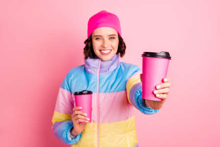 Portrait of her she nice attractive cheerful cheery girl holding in hands two take-out cups of green herbal tea giving to you isolated over pink pastel background