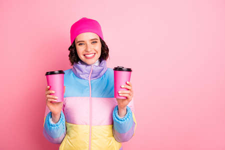 Portrait of her she nice attractive lovely cheerful cheery girl holding in hands two take-away cups of green tea isolated over pink background 写真素材