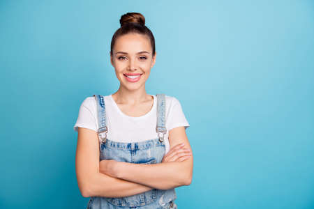 Portrait of charming entrepreneur with her hands folded wearing white t-shirt denim jeans isolated over blue background