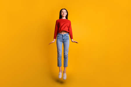 Full length body size photo of cheerful cute nice gorgeous attractive girl starting to fly up in footwear smiling toothily jumping isolated over yellow vivid color background