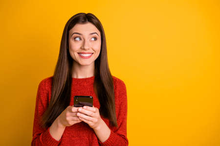 Photo of beautiful cute trendy charming pretty girl holding telephone pondering over like she just got staring into empty space isolated over vivid color background yellow