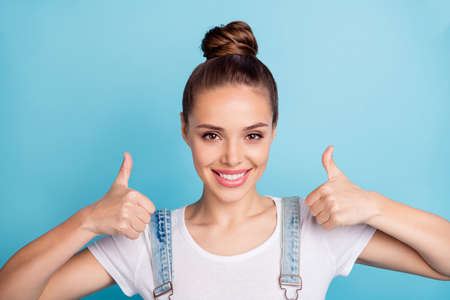 Close up photo of lovely girl showing thumb up smiling wearing white t-shirt denim jeans overalls isolated over blue background