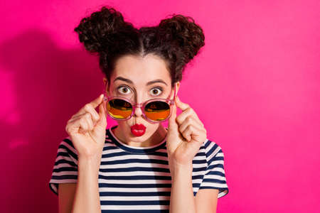 Nahaufnahmeporträt von ihr, sie sieht hübsch aus, attraktiv, glamourös, hübsches, mädchenhaftes Mädchen, das die Spezifikationen berührt, die einen Kuss einzeln über hell leuchtendem, leuchtendem rosa Fuchsia-Farbhintergrund senden Standard-Bild