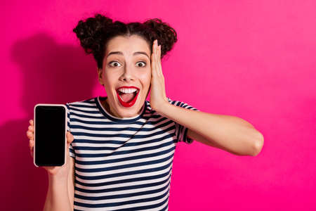 Photo of wavy cheerful positive funky girlfriend wearing striped clothing showing you phone screen shocked trendy facial expression isolated over vivid color fuchsia background