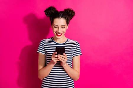 Photo of cheerful cute nice charming girlfriend browsing through her phone isolated over vivid fuchsia bright color background