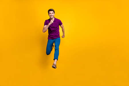 Full length body size photo of cheerful positive attractive handsome guy wearing blue pants trousers purple t-shirt footwear expressing positive emotions isolated vivid color background