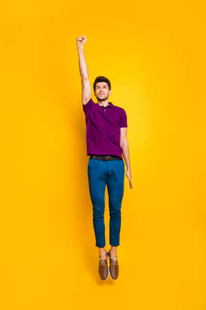 Vertical full length body size view of his he nice attractive purposeful strong guy jumping up flying isolated over bright vivid shine vibrant yellow color background Stock Photo