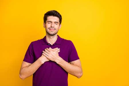 Portrait de son homme gentil, gentil et paisible, reconnaissant, vêtu d'une chemise lilas touchant le cœur, les yeux fermés, isolés sur fond de couleur jaune vif et brillant