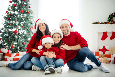 Portrait of four nice attractive idyllic affectionate cheerful big full adopted foster family celebrating newyear enjoying winter december vacation weekend in light white interior living-room Stock Photo