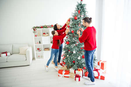 Full length body size view portrait of three nice attractive lovely sweet charming, cheerful cheery family spending winter December leisure decorating in modern light white interior living-room