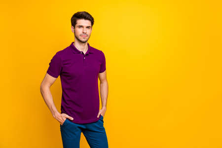 Portrait of his he nice attractive content serious guy wearing violet shirt holding hands in pockets isolated on bright vivid shine vibrant yellow color background