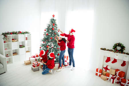Full length body size above high angle view of four nice attractive lovely, dreamy big idyllic affectionate family celebrating newyear enjoying leisure tradition light white interior living-room