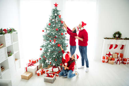 Full length body size above high angle view of four nice cheerful dreamy, big full foster affectionate family celebrating newyear enjoying leisure domestic tradition in light white interior room Stock Photo