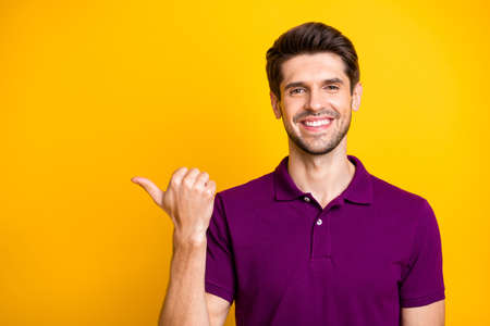 Close-up portrait of his he nice attractive content cheerful cheery glad guy wearing lilac shirt pointing thumb aside advert like isolated over bright vivid shine vibrant yellow color background Stock fotó