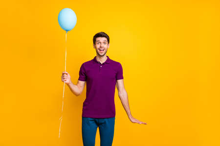 Photo of cheerful positive casual handsome man holding air ball of helium with hands wearing, pants trousers blue isolated over vivid color background