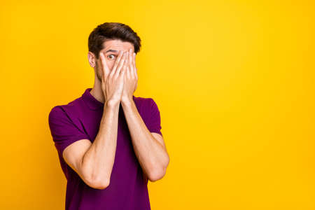 Portret van zijn aardige, aantrekkelijke, bange man met een violet shirt die zijn gezicht in de handpalmen verbergt en gluren geïsoleerd op een heldere, levendige glans, een levendige, gele kleurachtergrond Stockfoto