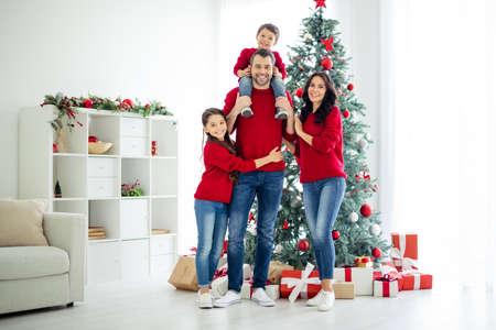 Foto de cuerpo entero de la gran familia encantadora de colegiala abrazar a su papá, llevar a un niño más pequeño y a mamá a celebrar las fiestas navideñas en casa con regalos en el interior