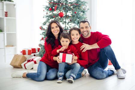 Foto de cuerpo entero de un gran papá encantador, mamá, colegiala, niño pequeño, sosteniendo el paquete para la noche de Navidad, disfrute de la Navidad con el cabello moreno con jeans de mezclilla rojos en casa en el interior Foto de archivo