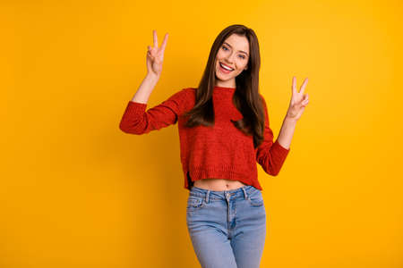 Photo of confident cheerful cute sweet lovely woman smiling toothily, showing you double v-sign isolated over yellow vibrant color background
