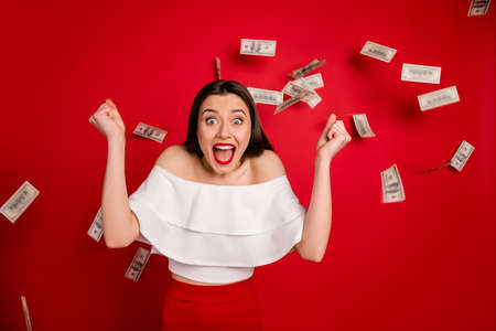 Portrait of cute lady raising, fists screaming wow omg wearing white off-shoulders isolated over red background Фото со стока