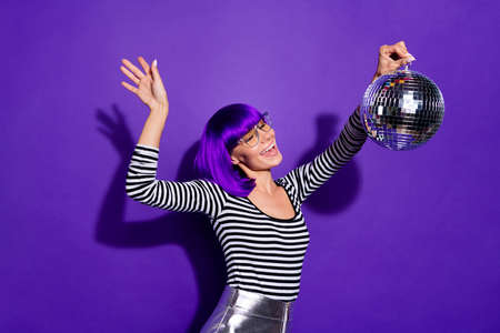Portrait of excited youth holding mirror ball screaming moving wearing, eyeglasses eyewear isolated over purple violet background