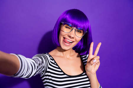 Portrait of charming youth making v-signs photo having trip wearing, striped shirt isolated over purple violet background Фото со стока